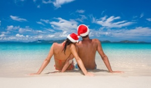 couple with merry christmas hats on romantic tropical beach for summer holiday